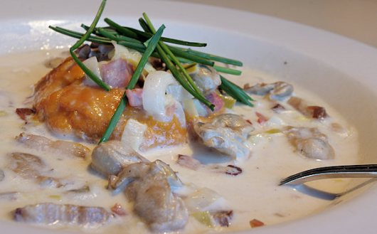 Our Oyster Pan Stew: Barcat oysters cooked in a country ham cream sauce with housemade bacon and pickled leeks, served over whipped sweet potatoes, and topped with chives.