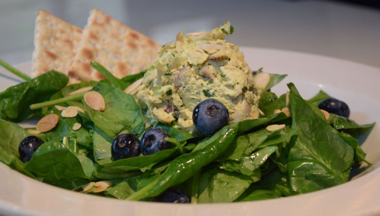 Curried Chicken Salad over baby spinach tossed in Meyer lemon vinaigrette, topped with fresh blueberries and sliced almonds